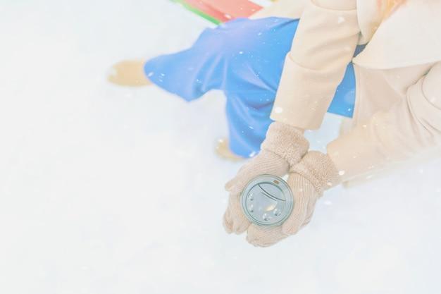 Femme en manteau beige, pantalon bleu, mitaines chaudes boit du café chaud pour aller enneigé
