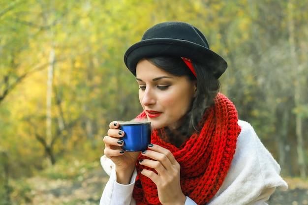 Une femme en manteau blanc au crochet écharpe rouge et chapeau noir tient une tasse dans ses mains tea party