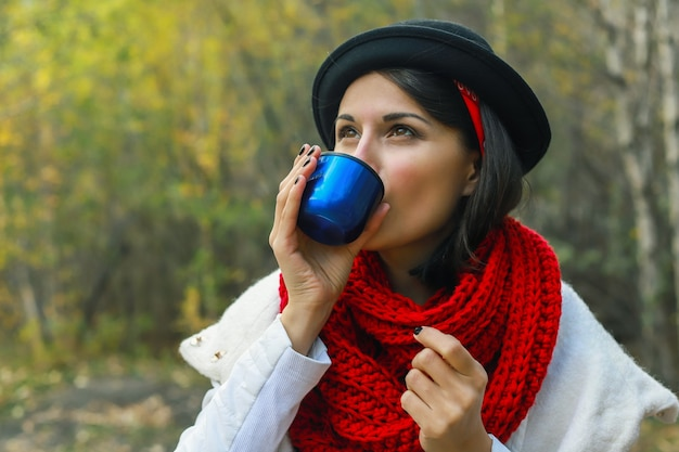 Femme en manteau blanc crochet écharpe rouge et chapeau noir tient une tasse de thé dans ses mains pique-nique en plein air