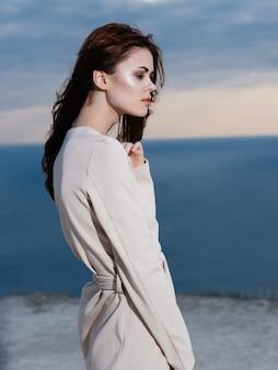 Femme en manteau glamour posant le paysage d'été de l'océan. photo de haute qualité