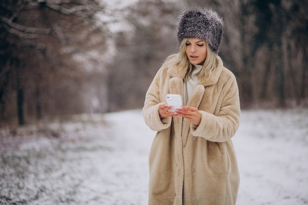 Femme en manteau d'hiver marchant dans un parc plein de neige parlant au téléphone