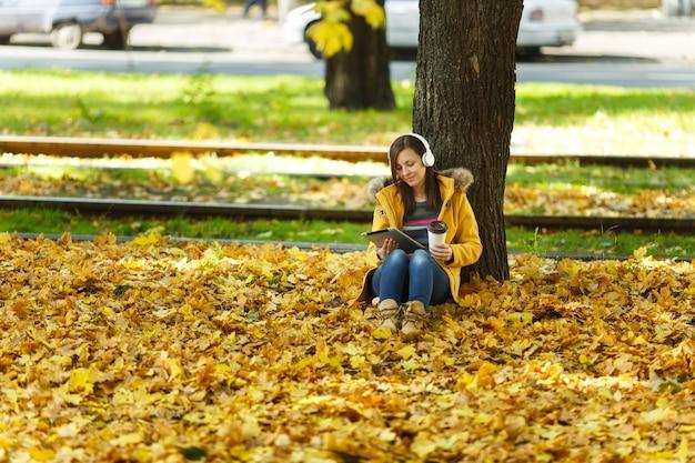 Une femme en manteau jaune et jeans assis avec une tasse de café ou de thé et écoutant de la musique sous un arbre avec une tablette dans les mains et des écouteurs dans le parc de la ville d'automne par une chaude journée. feuilles d'or d'automne.
