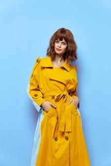 Femme en manteau jaune tient les mains dans les poches