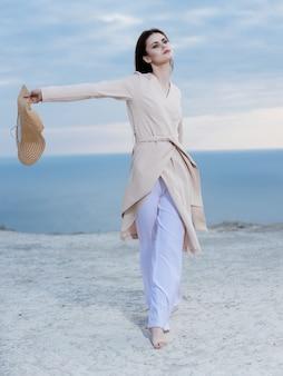 Femme en manteau nature plage à pied voyage océan