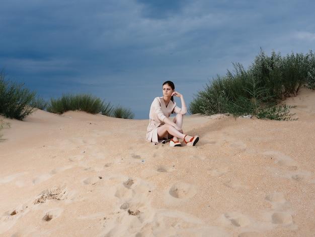Femme en manteau posant style élégant plage air frais