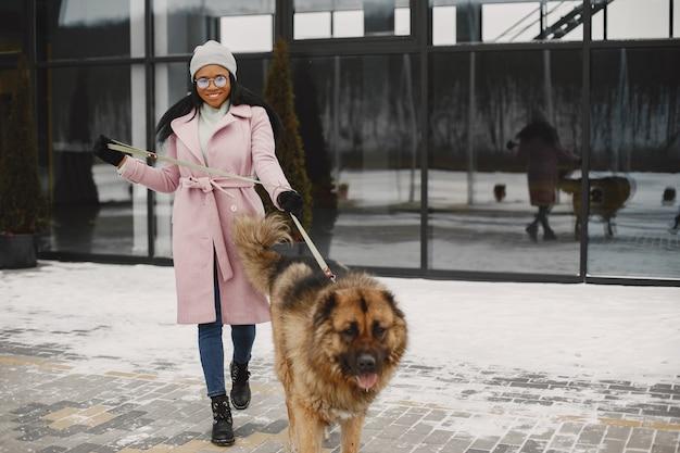 Femme en manteau rose avec chien