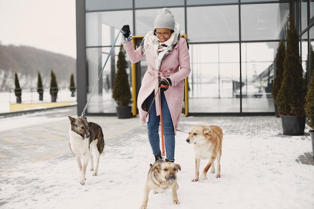 Femme en manteau rose, promener des chiens