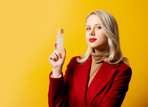 Femme en manteau rouge avec bouteille de lotion sur mur jaune