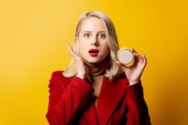 Femme en manteau rouge avec pot de crème sur mur jaune