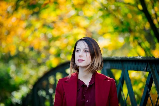 Femme en manteau rouge se reposer dans le parc autum
