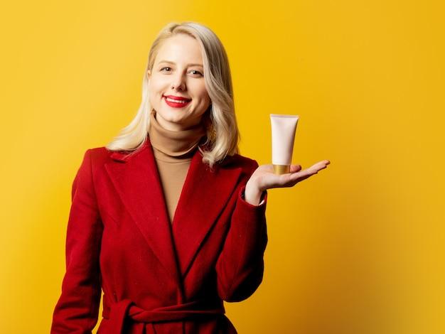 Femme en manteau rouge avec tube de crème sur mur jaune