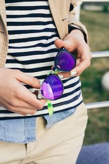 Femme en manteau et t-shirt rayé tenant des lunettes de soleil de couleurs vives