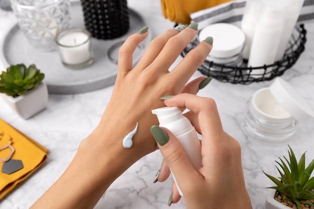 Femme avec manucure appliquer des cosmétiques sur sa main sur la table en marbre