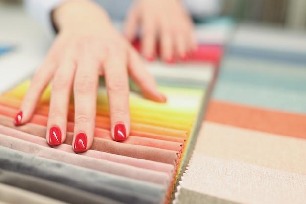 Femme avec manucure rouge choisissant un tissu pour coudre des rideaux en gros plan