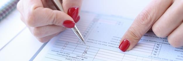 Femme avec manucure rouge remplissant le questionnaire libre