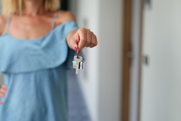Femme avec manucure rouge tenant les clés de l'appartement dans ses mains en gros plan