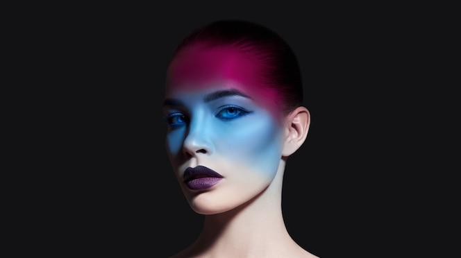 Femme de maquillage de beauté stricte lumineuse avec une ombre sur le visage dans des tons bleus et rouges. maquillage peau et visage parfaitement propres, rouge à lèvres foncé sur lèvres charnues