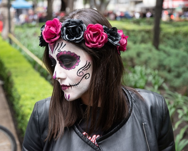 Femme avec maquillage catrina avec un diadème rose dans le jour traditionnel des morts à mexico