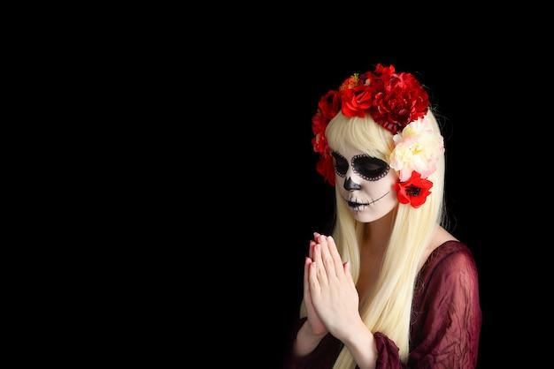 Femme avec maquillage de crâne de sucre et cheveux blonds isolés sur fond noir.