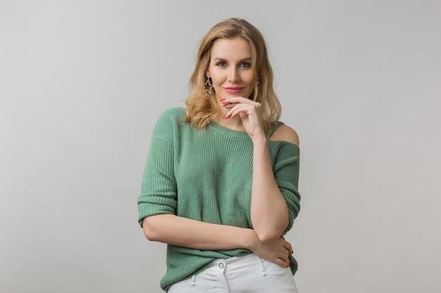 Femme avec maquillage élégant et pull vert posant sur rose