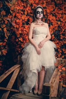 Femme avec maquillage fantôme et robe de mariée sur feuilles jaunes.