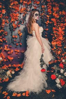 Femme avec maquillage fantôme et robe de mariée tenant un demi-côté rose.