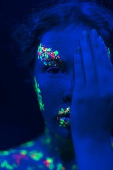 Femme avec maquillage fluorescent et main sur le visage