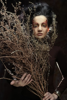 Femme avec un maquillage lumineux avec des branches sèches