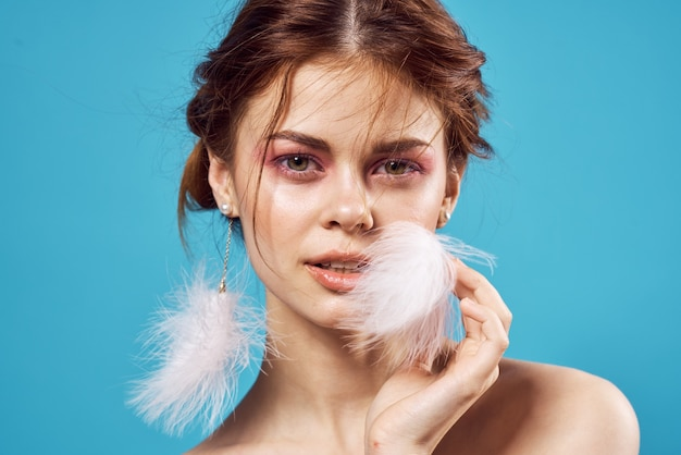 Femme avec un maquillage lumineux sur les épaules nues et des boucles d'oreilles moelleuses mode gros plan sur fond bleu
