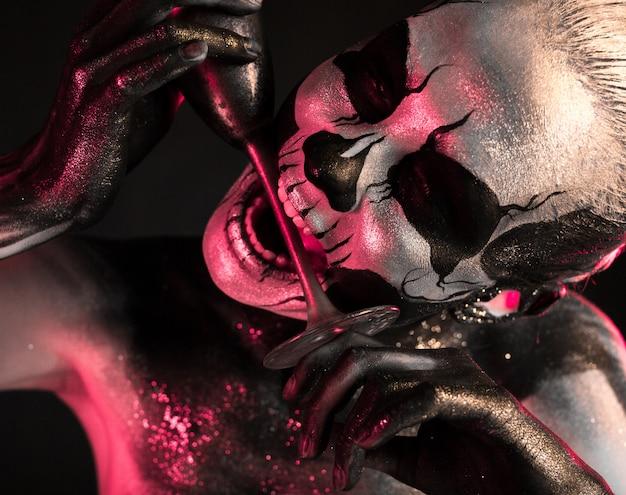 Femme avec maquillage squelette tient le verre
