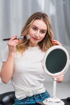 Femme maquillant devant un miroir