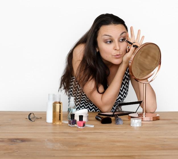 Femme maquillant son visage avec des produits de beauté