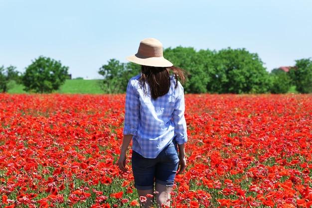 Femme marchant sur le champ de pavot sur le mur du ciel bleu