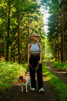 Femme marchant avec un chien dans une forêt en pologne