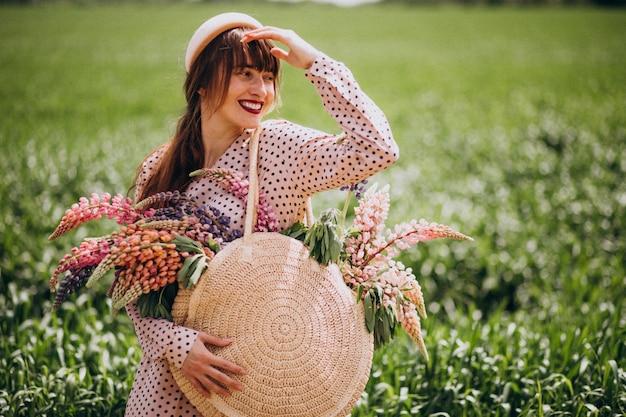 Femme marchant dans un champ avec des lupinus
