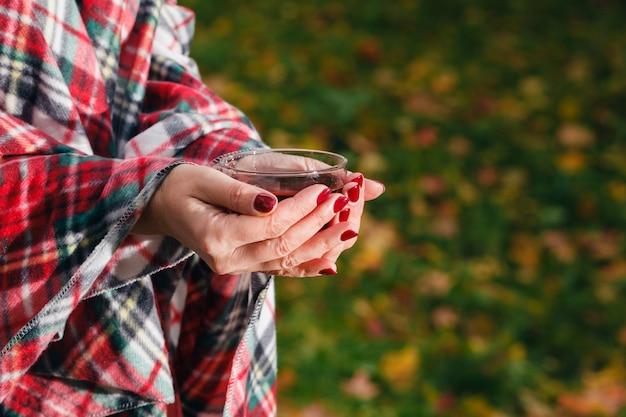 Femme marchant dans une couverture confortable dans le parc de l'automne
