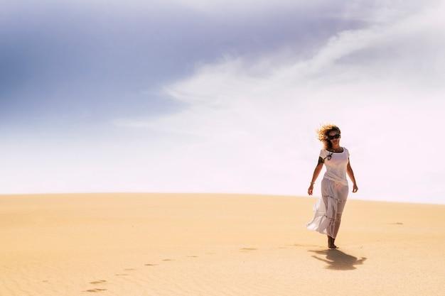 Femme marchant dans les dunes du désert du snd seul dans l'activité de loisirs de liberté seul