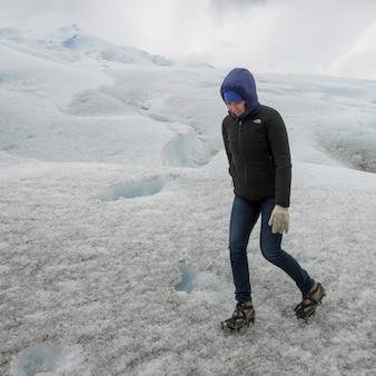 Femme marchant dans la glace sur le glacier perito moreno, parc national los glaciares, province de santa cruz, pat