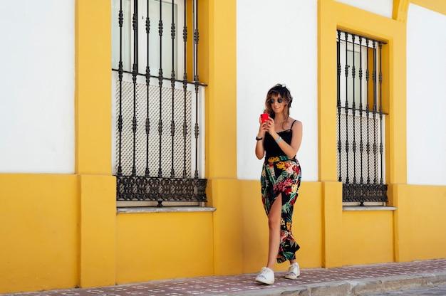 Femme marchant dans la rue en regardant le téléphone portable