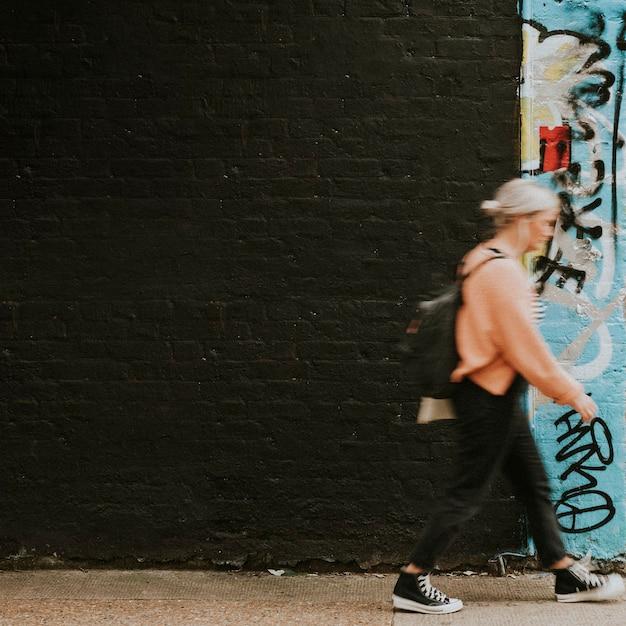Femme marchant devant la peinture murale d'art de rue