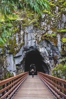 Femme marchant à l'intérieur d'un tunnel naturel à travers un pont