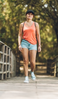 Femme marchant le long d'un chemin en bois dans des vêtements d'été