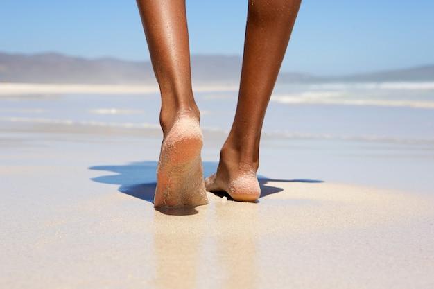 Femme marchant pieds nus sur la plage