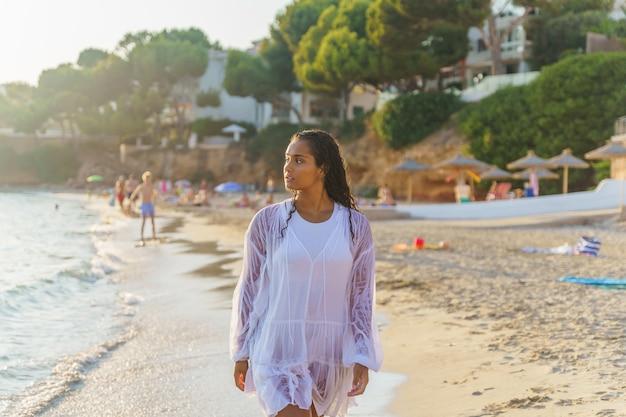 Femme marchant sur la plage en maillot de bain et robe