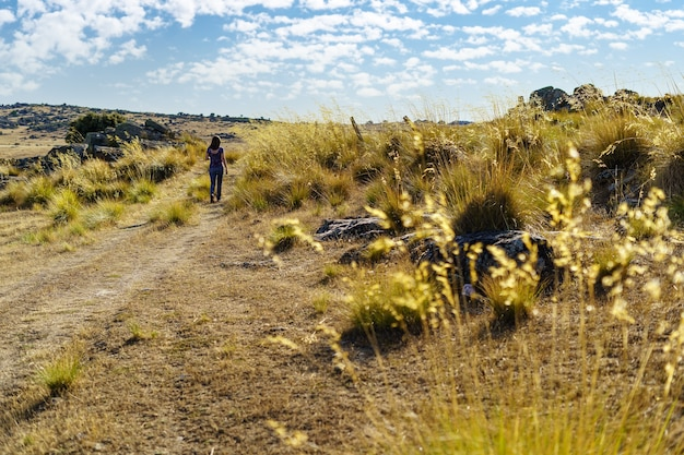 Femme marchant à reculons sur sentier dans le paysage d'été méditerranéen.
