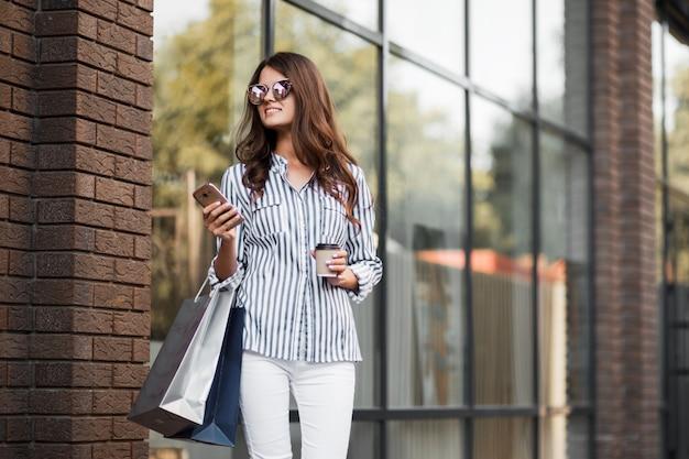 Femme marche après le shopping et utilise le téléphone.