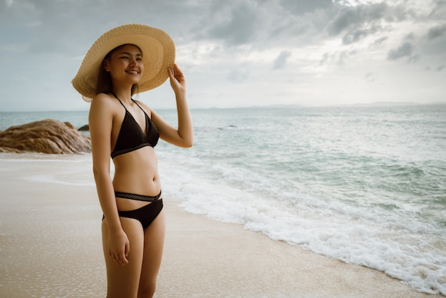 Femme, marche, bord mer, porter, bikini, porter, a, chapeau mer
