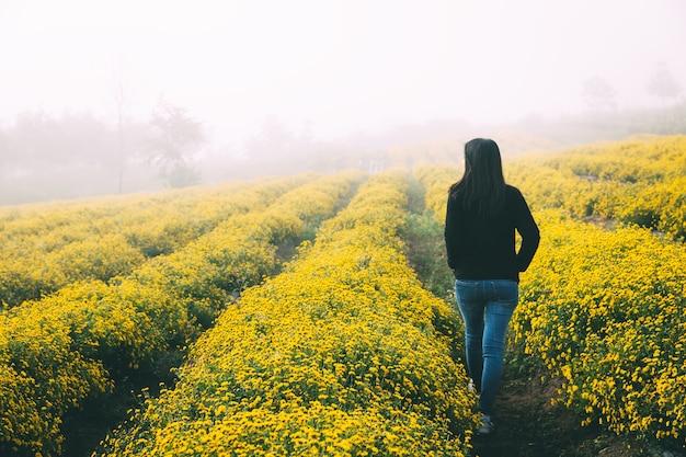 Femme marche, sur, champ fleur jaune