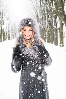 La femme marche dans l'allée du parc en hiver