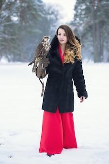 Une femme marche avec un faucon